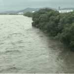 A flooding river in Kyushu reaches the top of the riverbank.