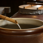 Shochu distillate pours into a earthenware pot.